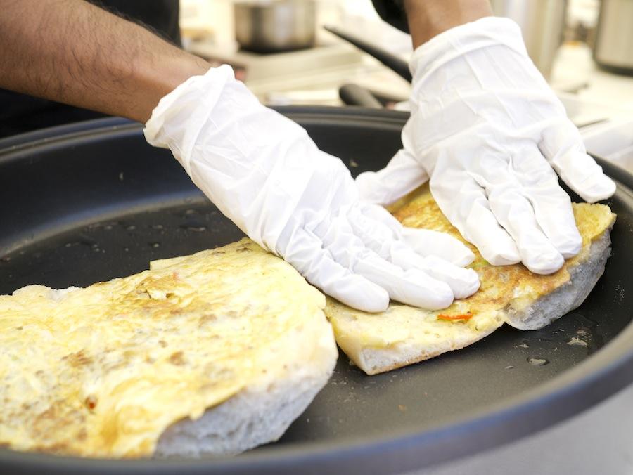 Der laves black pepper roti John, malaysisk inspireret omeletsandwich fra den kvindelige kok Devagi Sanmugam.