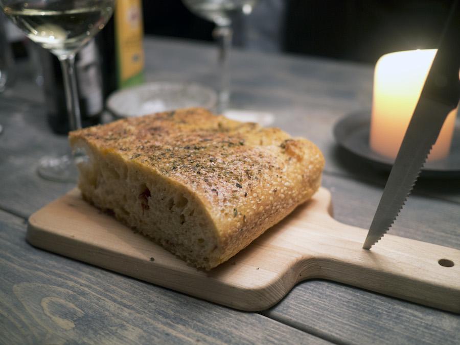 Foccacia med urter og dejligt fedtet og sprød skorpe. Der står olivenolie og balsamico på bordet, som du kan mikse i små skåle til at dyppe brødet i.