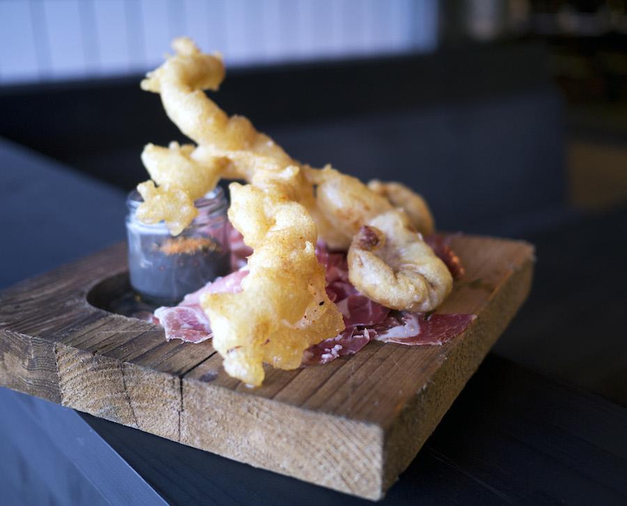 Blæksprutte efter en tur i den gyldne brønd med dejlig iberico-skinke underneden.