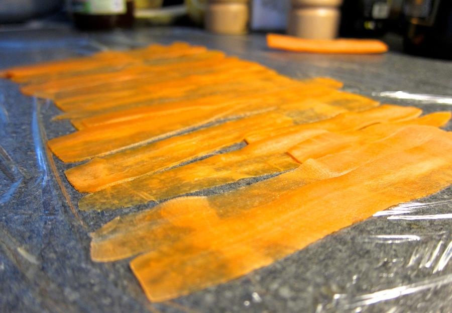 Maskinen snitter helt tyndt, her eksemplificeret ved gulerødder, der er skåret på langs.
